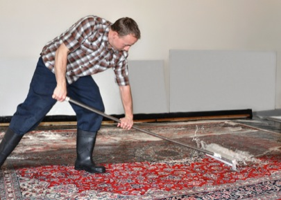 Picture of member of Imperial Rug Cleaning team cleaning a rug